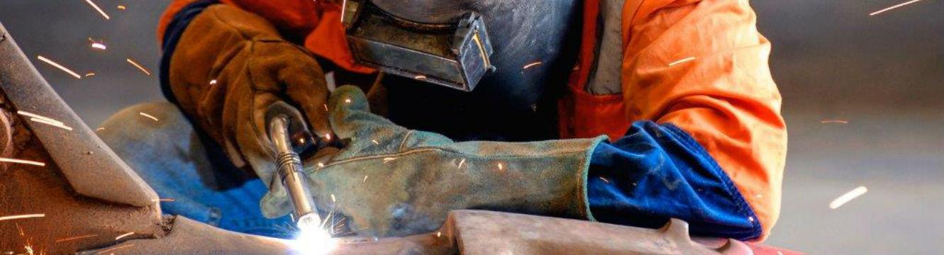 Un soudeur effectue une réparation d'un appareil avec pièces de métal