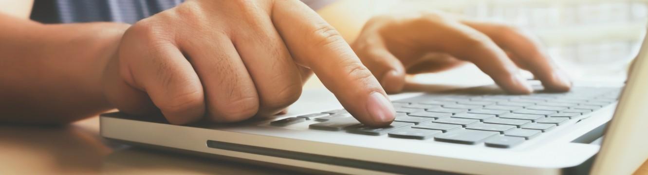 une personne ecrit sur un ordinateur