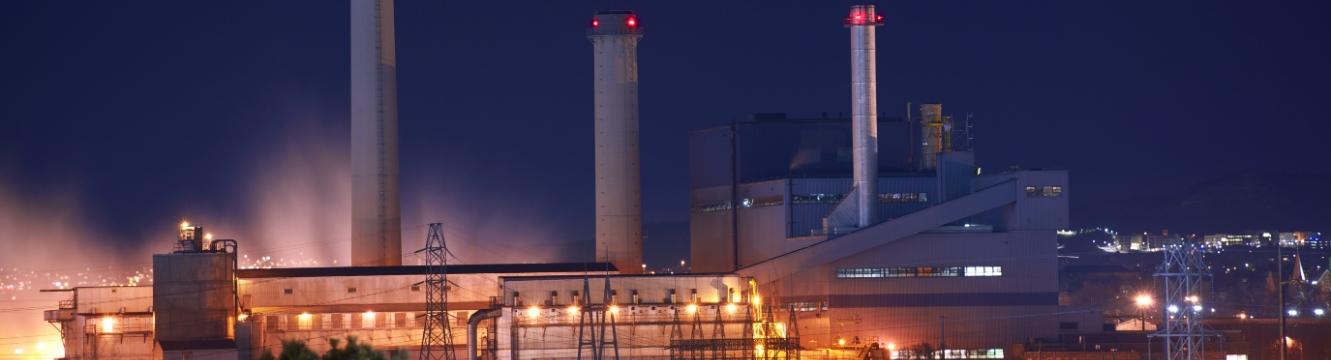 une usine dans la nuit éclairée par quelques lumières