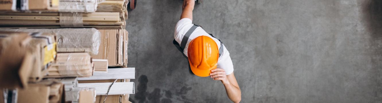 un employé tire un transpalette dans un entrepôt