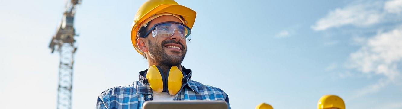 Un employé et deux collaborateurs travaillent sur un chantier pour la construction d'un bâtiment